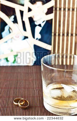Glas Alkohol und Trauringe