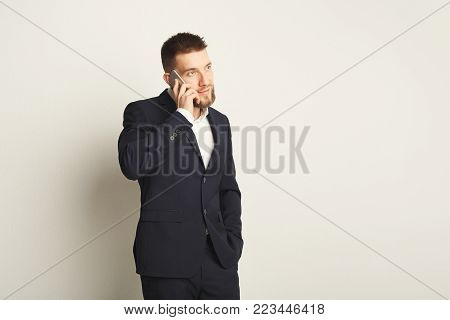 Handsome young caucasian businessman posing in studio and talking on mobile on white background. Confident serious man in formal clothes, copy space, isolated