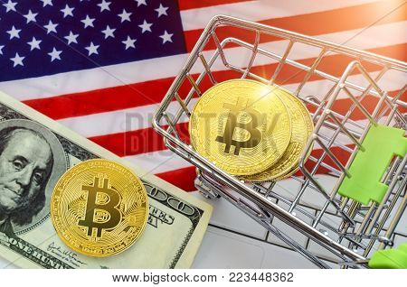 bitcoin trading concept; shopping trolley with coins bitcoin on the keyboard near the American (USA) flag and one hundred (100$) dollar bills