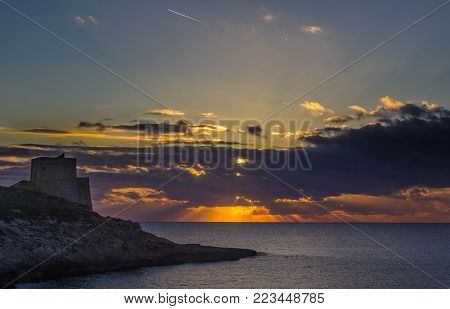 Crepuscular rays at sunset, with Xlendi tower in the foreground