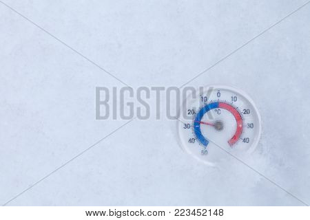 Frozen thermometer with celsius scale in snow showing extreme low sub-zero temperature minus 25 degree a cold winter weather concept