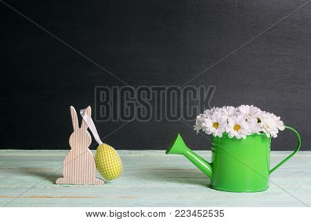 Daisies bouquet and a bunny with Easter egg - Cute white daisies arrangement in a watering can and a wooden bunny with a yellow fabric egg hanging, on a green table and a black background.