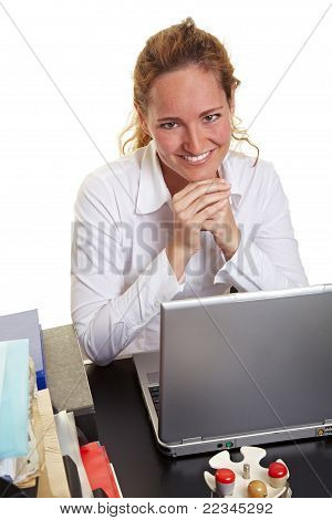 Smiling Business Woman Behind Her Desk