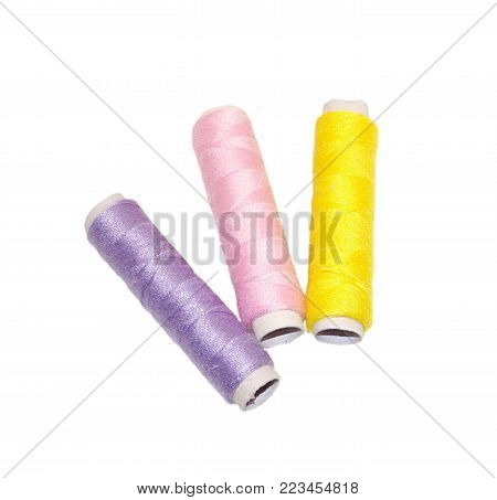 Few small shiny coils of different colored cotton thread isolated on white background