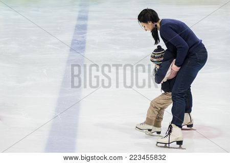 Happy family, mother teaches son ice skating at rink. Winter activities