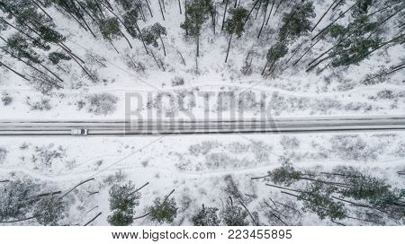 Car driving on the road in the winter forest. Top view
