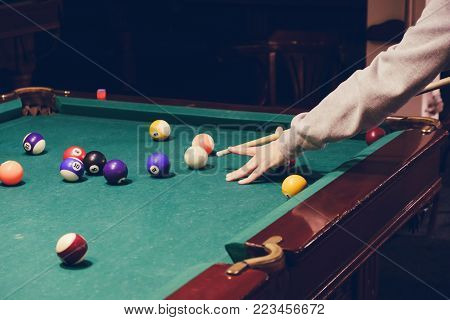 Hand holding billiard stick cue on a pool table ready to shot the ball