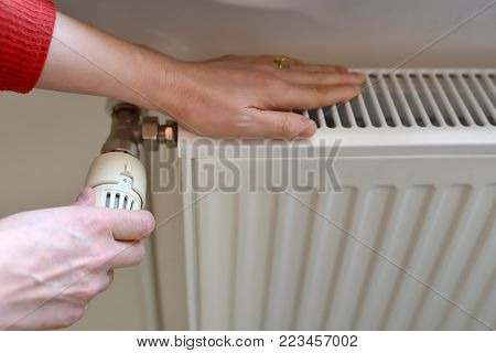 Woman programming temperature on Radiator, close up