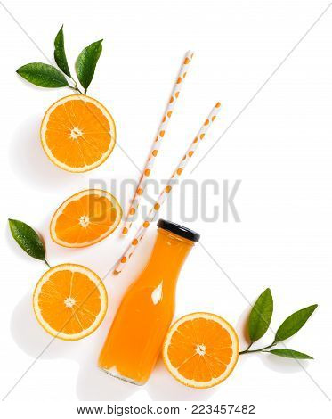 Top view of freshly squeezed orange juice in a glass bottle,drinking straws and orange slice with green leaves isolated on white background.
