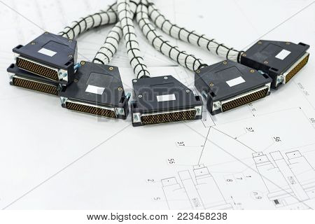Multi-pin cable connectors. A bundle of cable harnesses lies on the table.