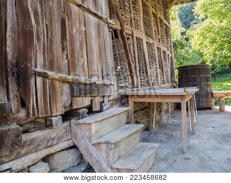 Part of an old wooden barn with a barrel and table with an apple on it in front, at Baba Stana Neighborhood, Oreshak, Bulgaria