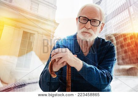 Calm pensioner. Thoughtful calm senior man sitting on the comfortable bed with his hands on the walking stick and looking relaxed
