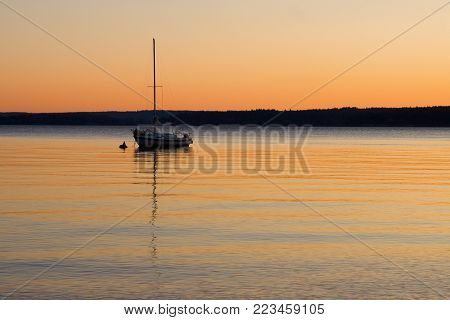 A sailboat anchored on calm waters at sunset