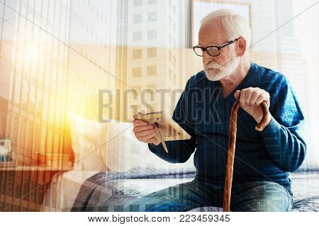 Old photo. Senior thoughtful man sitting on a comfortable bed with his hand on a walking stick and looking at the old photo in wooden frame