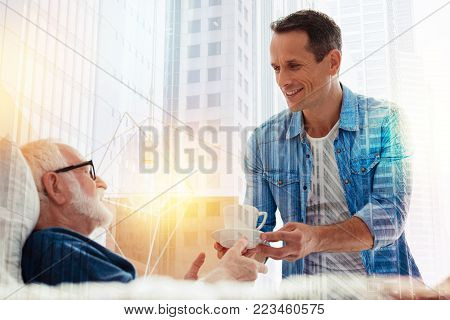 Help yourself. Kind attentive cheerful man looking friendly while standing near the bed of his calm aged father and giving him a cup of coffee
