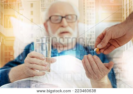 Taking pills. Calm responsible senior man wishing to recover while staying in bed and holding a glass of water before taking his pills