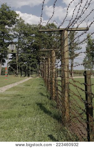 Barbed wire fence with patrol watchtower in background in near Druskininkai, Lithuania