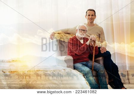 Close relatives. Calm serious aged man sitting in a comfortable armchair with his hands on a walking stick while his young handsome son sitting next to him and smiling
