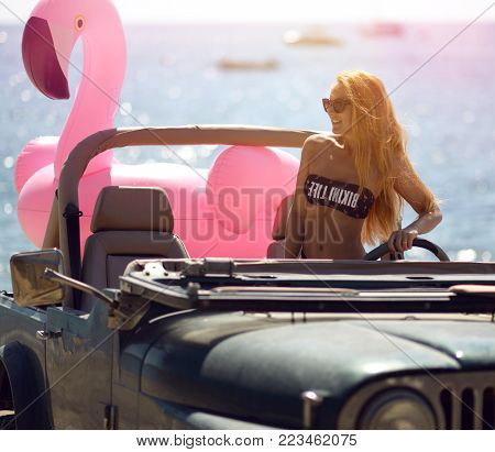 Happy beautiful young girl in sunglasses sitting in beach truck car on sunny summer day near sea beach with giant inflatable giant pink flamingo float mattress