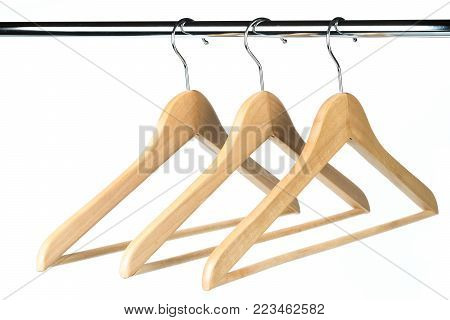 Three wooden coat / clothes hangers on a clothes rail with a white background. Potential copy space to the left of hangers.