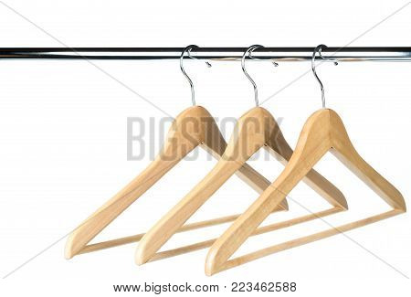 Three empty wooden coat /clothes hangers on a clothes rail with a white background. Potential copy space above and to the left of hangers.