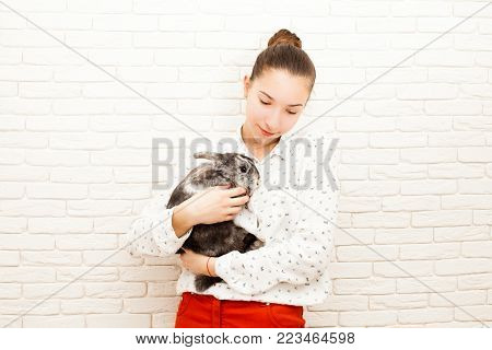 Girl holding a real Lop-eared rabbit and smilling