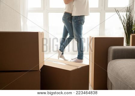 Moving boxes with couple embracing at background, boyfriend and girlfriend starting new life in own bought rental apartment, homeowners packed belongings to move ready for relocation, close up view