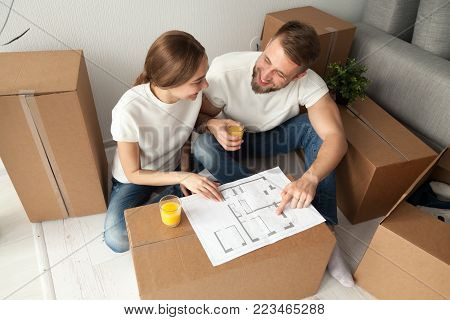 Happy couple discussing house plan looking at blueprint planning new home interior design, happy homeowners share furnishing remodeling ideas sitting on floor with moving boxes drinking orange juice
