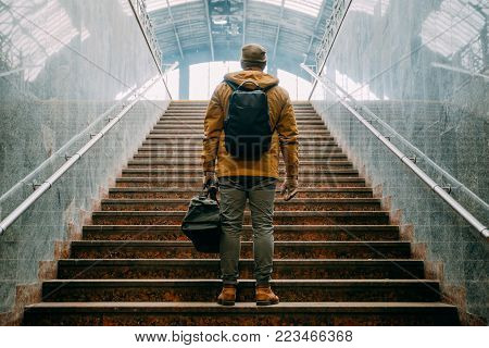man climb stairs with bags in hand to railway station