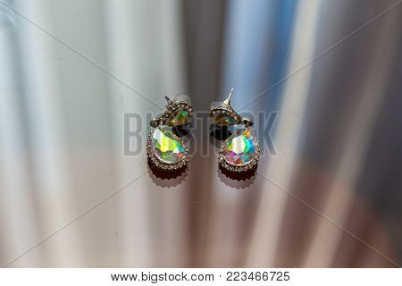 Earrings with diamonds macros are lying on the glass and shine in the sun in different colors