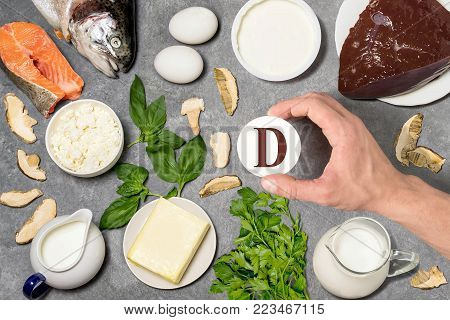 Food rich in vitamin D. Various natural sources of vitamins. Useful food for health and balanced diet. Prevention of avitaminosis. Man's hand holds tag with name of vitamin D. Top view