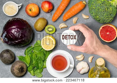 Food for detoxification. Detox food purify body of toxins, have beneficial health effects. Concept of purification. Man's hand holds tag with word detox. Top view
