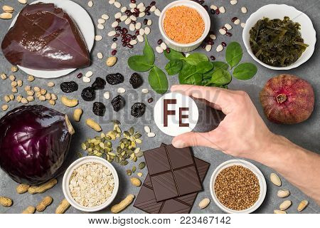 Food rich in ferrum. Various natural sources of vitamins and micronutrients. Useful food for health and balanced diet. Prevention of avitaminosis. Man's hand holds tag with name of ferrum. Top view