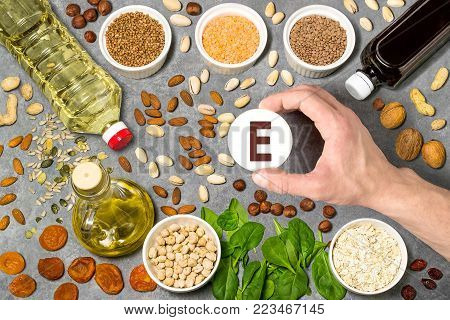 Food rich in vitamin E. Various natural sources of vitamins. Useful food for health and balanced diet. Prevention of avitaminosis. Man's hand holds tag with name of vitamin E. Top view