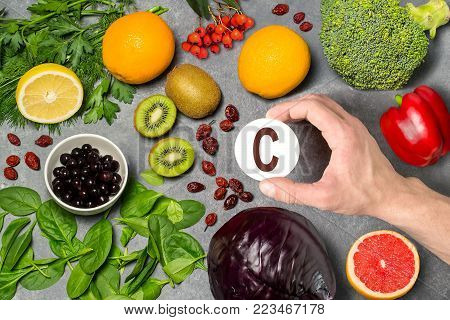Food rich in vitamin C. Various natural sources of vitamins. Useful food for health and balanced diet. Prevention of avitaminosis. Man's hand holds tag with name of vitamin C. Top view