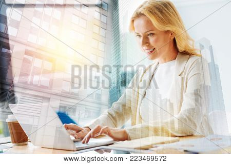 Dedicated to job. Portrait of admirable smiling woman sitting in front of a laptop and typing while being fully concentrated on working
