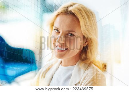 Incredible mood. Close up of adorable woman expressing optimism and kindness while smiling at you