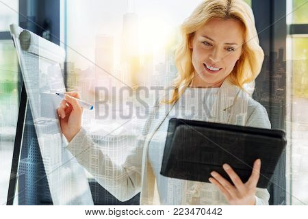 Splendid idea. Portrait of pleasant woman being busy using a board and writing down information while looking at the tablet screen