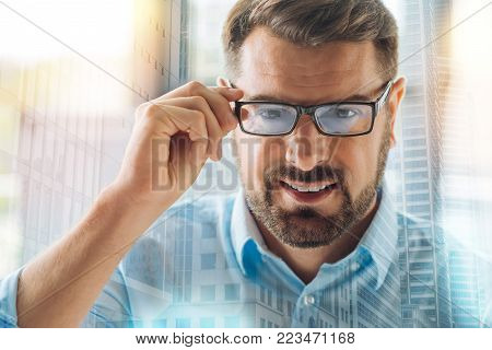 Shrewd glance. Close up of successful bearded director looking at you with a smile while wearing glasses and touching the glasses frame