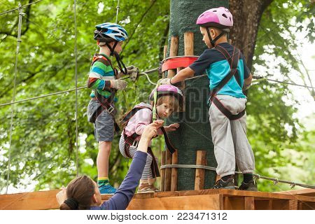 Group of children in a helmet and safety equipment in adventure ropes park. Camping leisure