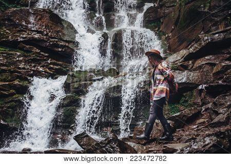 wanderlust and travel concept. stylish traveler girl holding hat looking at waterfall, exploring woods. hipster woman with backpack travelling at river in forest. space for text poster