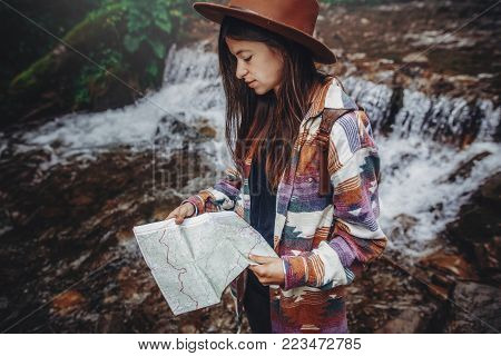 wanderlust and travel concept. stylish traveler girl in hat looking at map, exploring woods. hipster woman with backpack travelling at river in forest. space for text poster