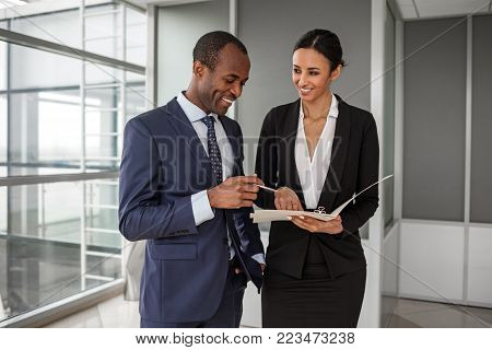Project management. Joyful young business partners wearing official clothes are working together. Charming lady is holding papers while african man keeping pen and looking at folder with smile
