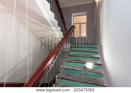 Stairs with wooden banisters is the part of interior of apartment during  upgrade  or  remodeling, renovation, extension, restoration, reconstruction and construction and portable lamp for lighting the working place. poster