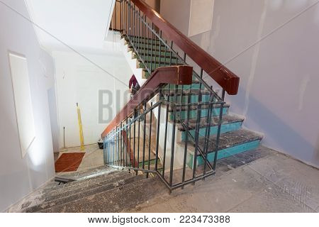 Stairs with wooden banisters is the part of interior of apartment during  upgrade  or  remodeling, renovation, extension, restoration, reconstruction and construction and portable lamp for lighting the working place.