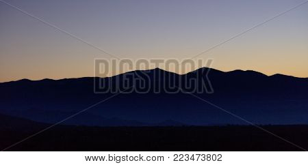Sunset or sunrise over mountains silhouette with blue sky backdrop. Panoramic view, banner.