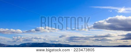 Blue sky backdrop with hanging clouds over mountains silhouette. Aerial, panoramic, banner photo.