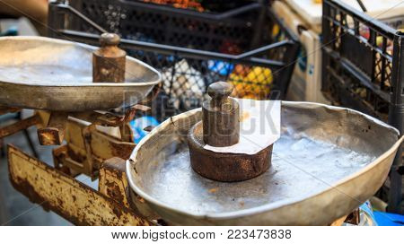 Old style scale with rusty weights on it. Close up view with detail, blur plastic lattice background