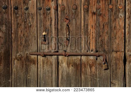 Wooden brown door. Timeworn blank, banner, background with rusty latch and padlock. Closeup, details
