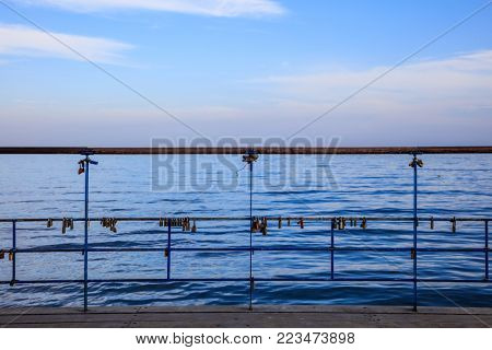 Rusty padlocks locks on peeled railing. Tradition for couple in love. Blue sky and sea backdrop.